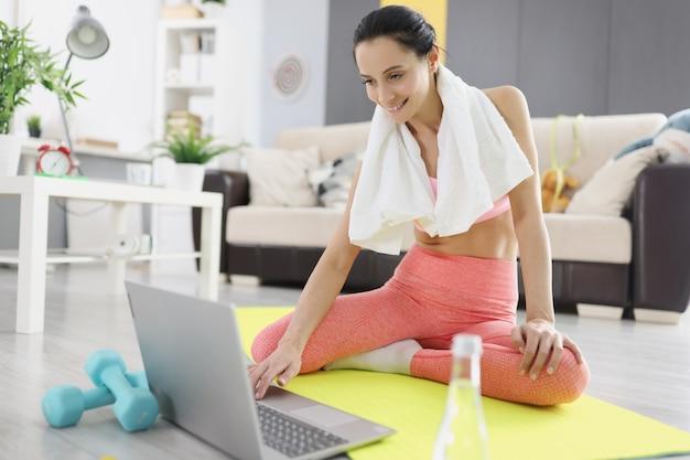 목에 수건을 두른 젊은 여성이 노트북 앞에서 집에서 스포츠 운동을 하고 있습니다. covid 19 전염병 개념 중 원격 피트니스