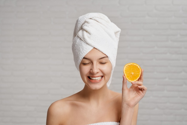 Young woman with towel on head keeping fresh orange in hand