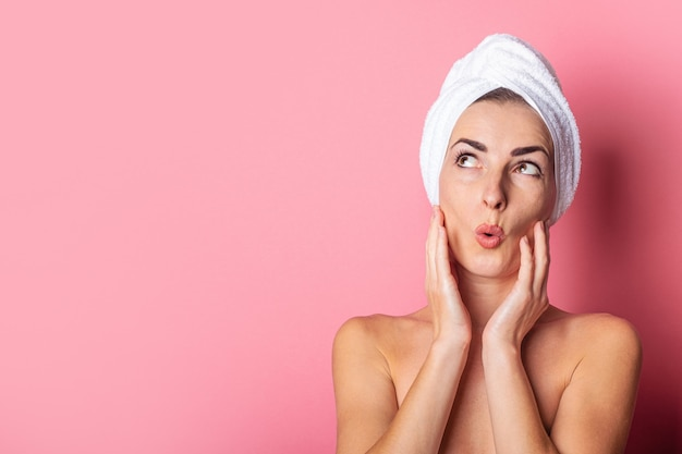 Young woman with a towel on her head, bare shoulders, looks up in surprise on a pink background.