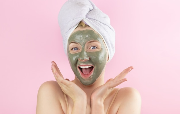 A young woman with a towel on her head and a clay mask on her face on a pink background