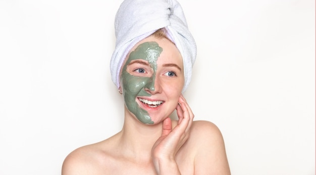 A young woman with a towel on her head, half of her face in a clay mask