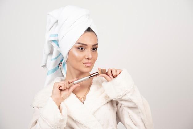 Giovane donna con un asciugamano in testa e una nappa.
