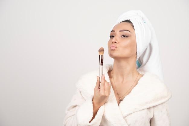 Giovane donna con un asciugamano in testa e una nappa