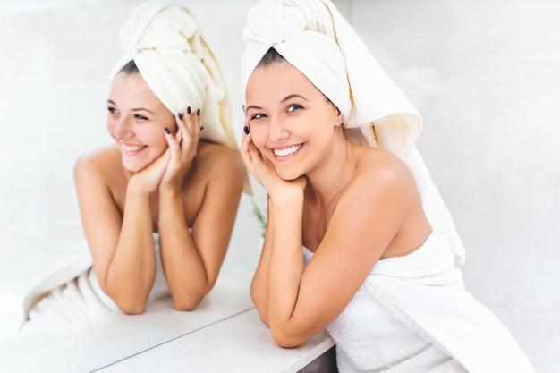 鏡の横に頭にタオルを持つ若い女性