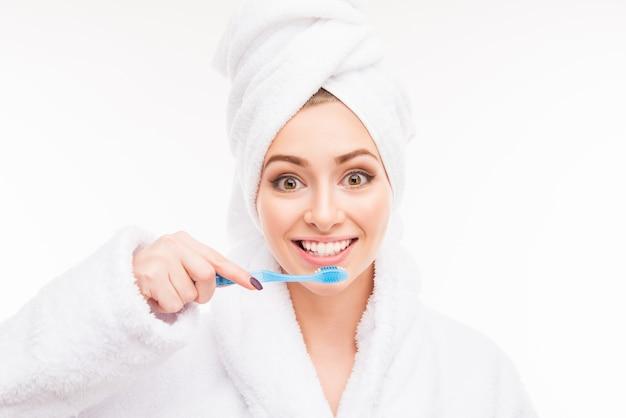歯ブラシを保持している彼女の頭にタオルを持つ若い女性