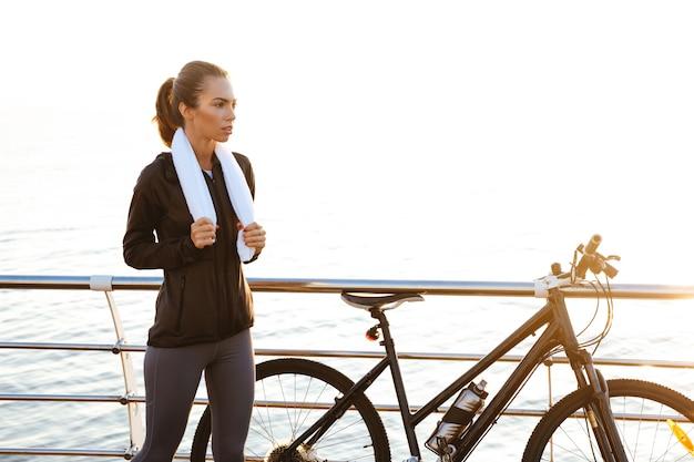 Молодая женщина с полотенцем на шее стоит возле велосипеда на открытом воздухе после тренировки на берегу океана