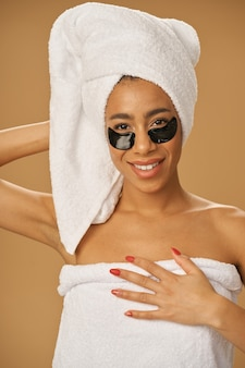 Young woman with towel wrap smiling at camera, posing with applied black beauty patches under eyes