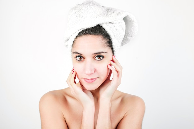Young woman with a towel wrapped around her head against white background