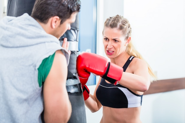Young woman with trainer in boxing sparring