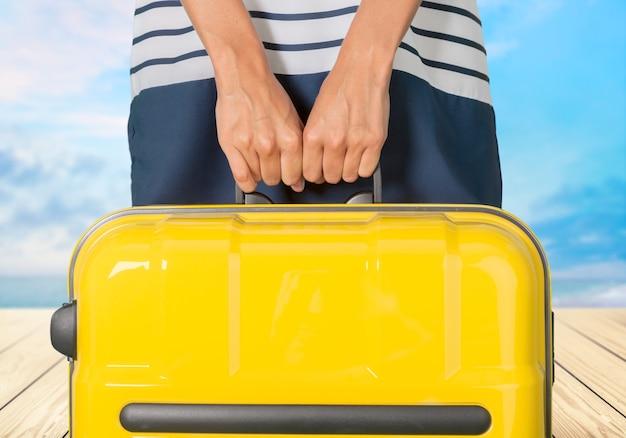 背景に旅行バッグを持つ若い女性