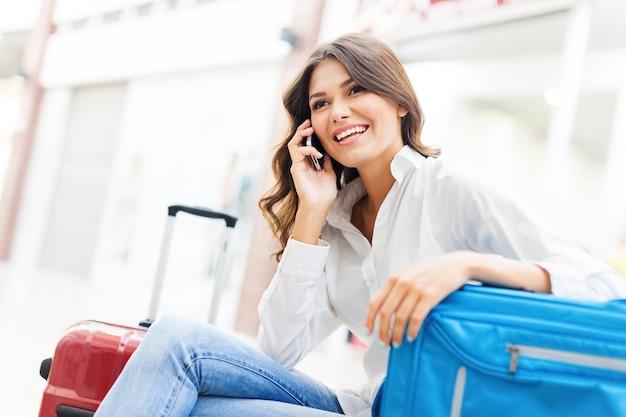 배경에 여행 가방을 든 젊은 여성