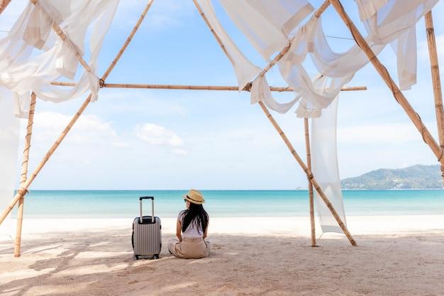 Молодая женщина с чемоданом путешествия сидит на пляже летом.
