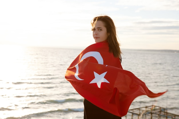 Young woman with turkish flag on sky and sea