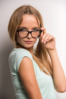 Young woman with two tails and glasses is posing.