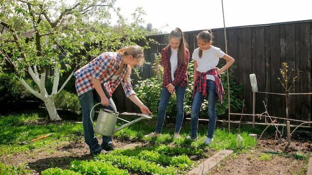 정원에서 야채를 급수 두 십 대 자매와 젊은 여자.
