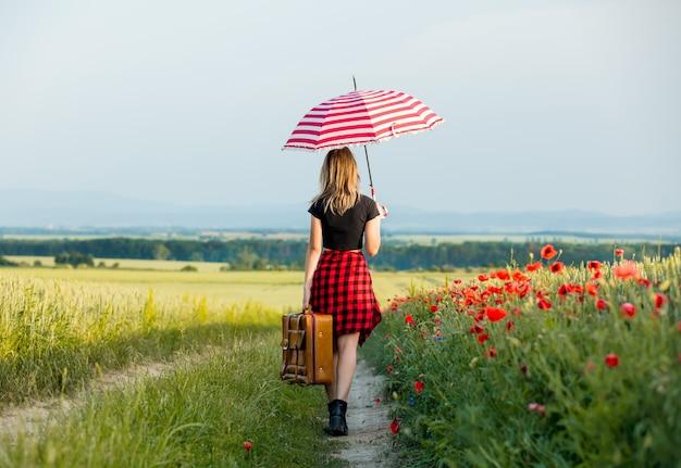 시골 길을 걷고 있는 우산과 가방을 든 젊은 여자