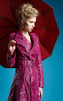Young woman with umbrella on blue