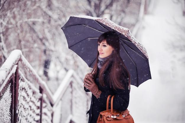 폭설에 우산을 쓴 젊은 여성, 복고풍 톤 이미지