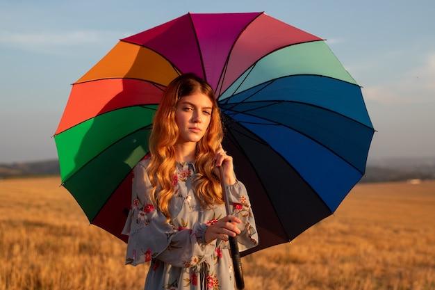 Молодая женщина с зонтиком в поле