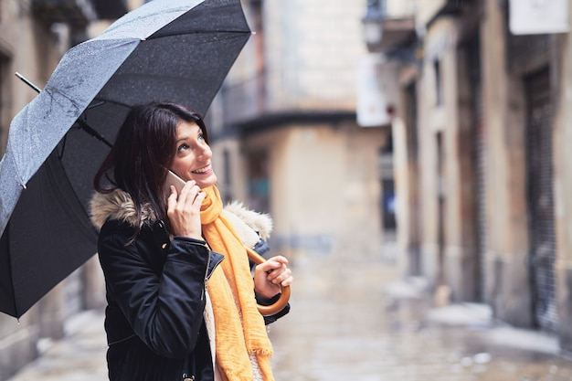 A young woman with an umbrella and using her mobile phone on a rainy day at an urban scene
