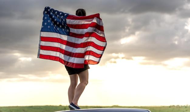 Молодая женщина с флагом сша, наслаждаясь закатом в природе.
