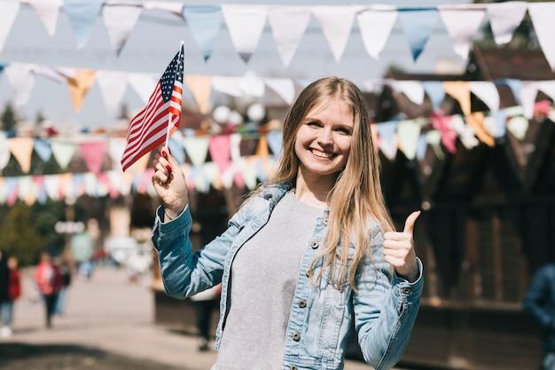 祭りでアメリカ国旗を持つ若い女