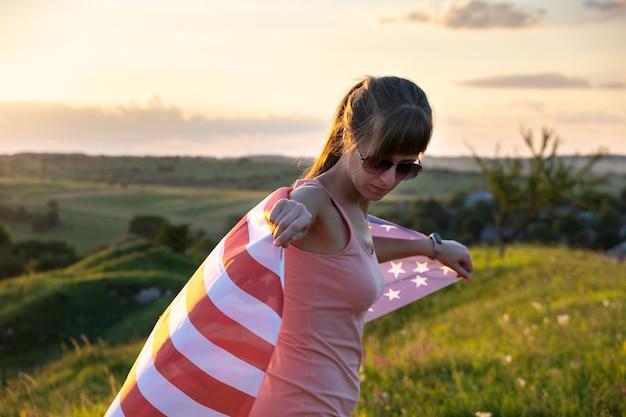 Молодая женщина с национальным флагом сша, стоя на открытом воздухе на закате.