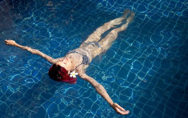 활기찬 핑크 머리 스파 리조트 수영장에서 편안한 젊은 여자