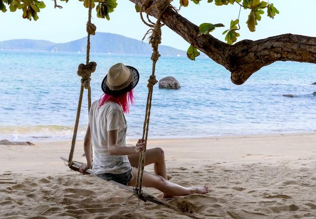 활기찬 핑크 머리 바다 또는 바다 근처 스윙에서 편안한 젊은 여자. 여행 휴가 개념.