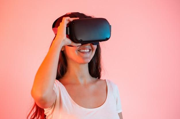 クローズアップから笑顔の目にバーチャルリアリティヘッドセットを持つ若い女性