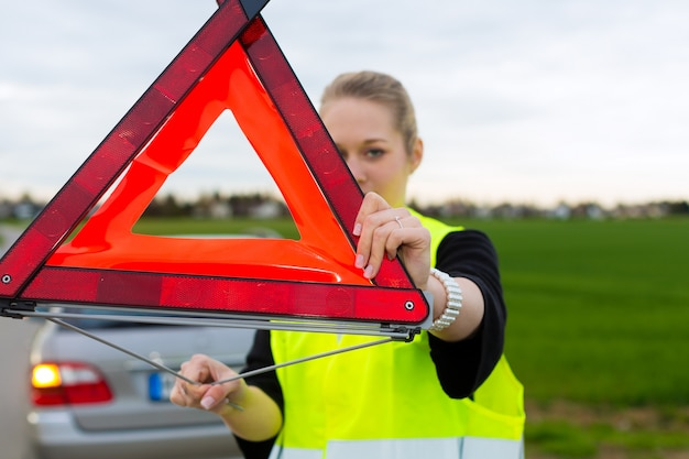 Young woman with warning triangle on street