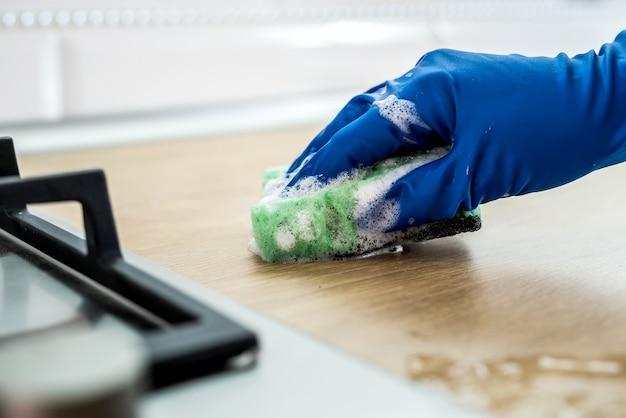 洗浄液とぼろきれを持った若い女性が台所で洗って掃除します。クリーニングのコンセプト。