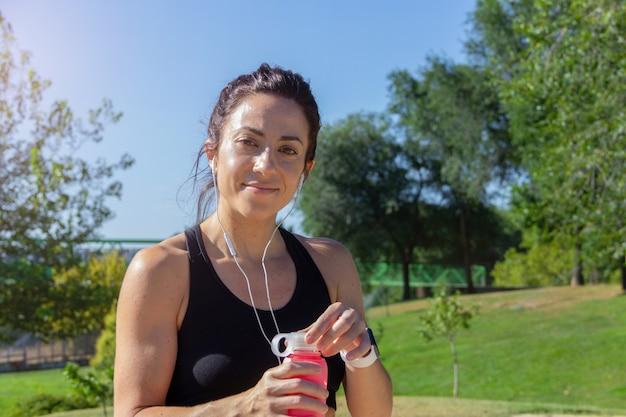 손에 물병을 든 젊은 여성이 카메라를 향해 미소 짓고 달리기 후 휴식을 취하고 있다