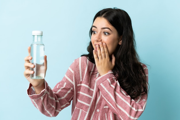 Young woman with a water isolated with surprise and shocked facial expression