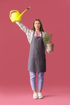 Young woman with watering can and houseplant on color