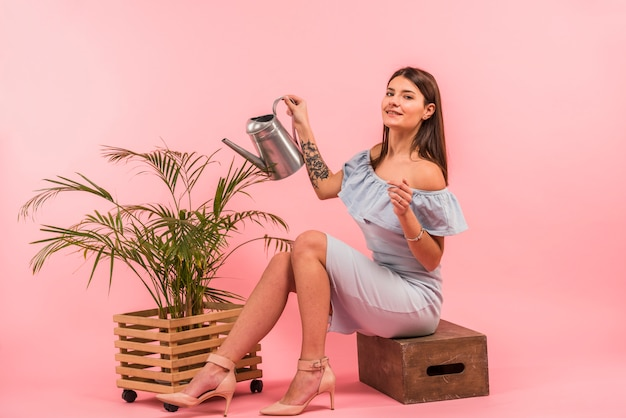 Young woman with watering can near houseplant