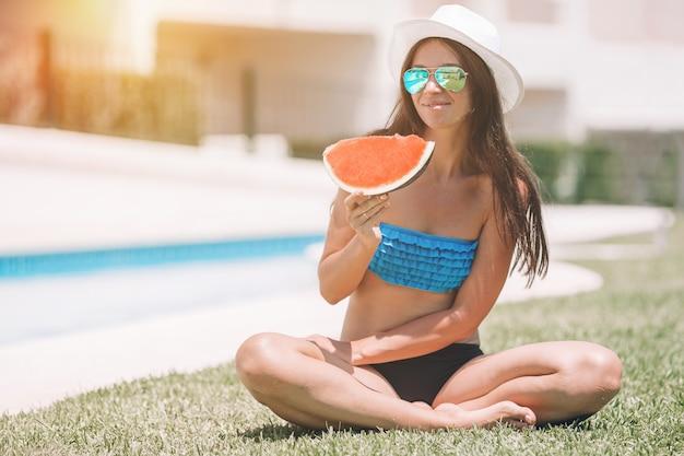 夏休みに屋外でリラックスしたスイカを持つ若い女性