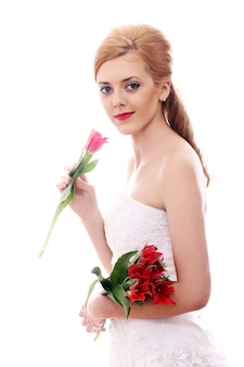 Giovane donna con abito da sposa e bouquet