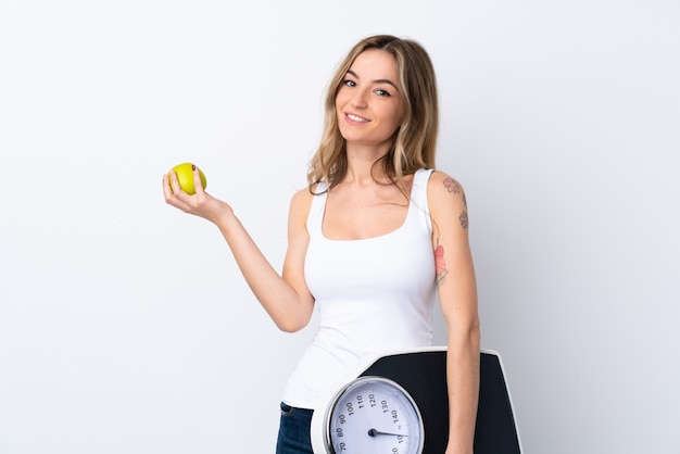Young woman with weighing machine and with an apple