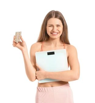 Молодая женщина с таблетками для похудения и весами на белом