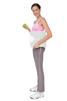 Young woman with weight scale and apple