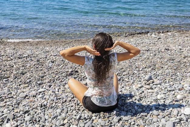 Молодая женщина с мокрыми волосами и в одежде сидит спиной в одиночестве на галечном берегу и тянется