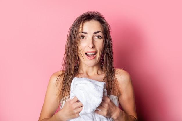 Молодая женщина с влажными волосами держит белое полотенце на розовом фоне.