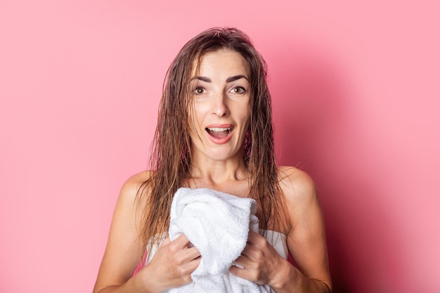 Young woman with wet hair holds a white towel on a pink background.