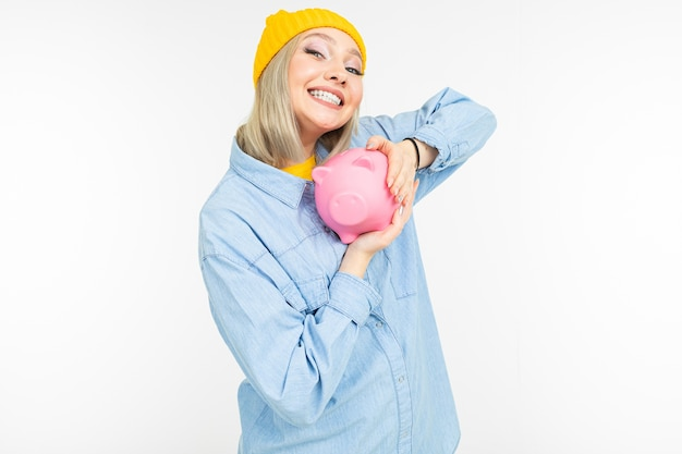 コピースペースのある白いスタジオの背景に財政を節約するための銀行と青いシャツの白い髪の若い女性。