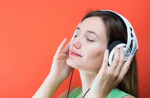 白いミュージカルヘッドフォンを持つ若い女性。