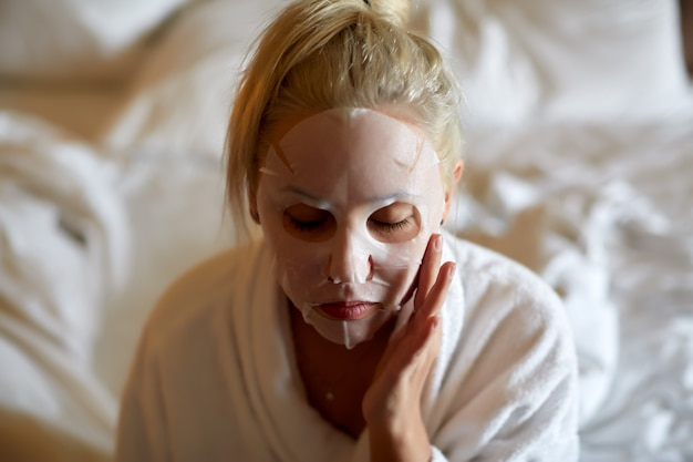 Young woman with white paper mask while sitting on bed at home.