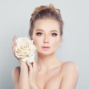 白いバラを持つ若い女性。スパモデル