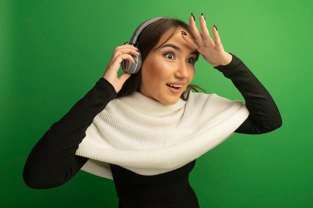흰색 스카프와 헤드폰이 행복하고 긍정적 인 머리 위로 손으로 멀리 찾고 젊은 여자