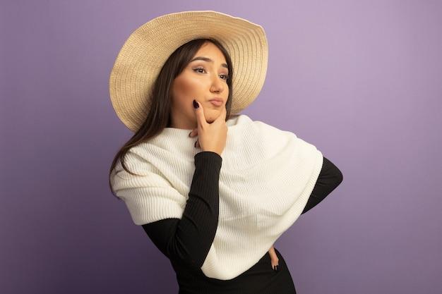 白いスカーフと夏の帽子を持つ若い女性は、紫色の壁の上に立って考えているあごに手を脇に見ています